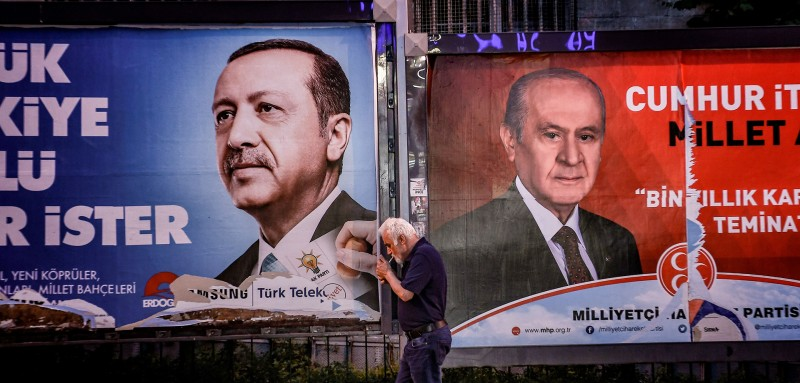 A pedestrian lights a cigarette as he walks past in banners with portraits of Turrkish President Recep Tayyip Erdogan (L) and the leader of Nationalist Movement Party (MHP) Devlet Bahceli in Istanbul on June 19, 2018. - Turkey is preparing for tight presidential and parliamentary elections on June 24, while many analysts say President Erdogan wants a major foreign policy success to give him a final boost. (Photo by Aris MESSINIS / AFP)        (Photo credit should read ARIS MESSINIS/AFP/Getty Images)