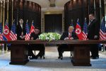 U.S. President Donald Trump and North Korean leader Kim Jong Un sign documents as U.S. Secretary of State Mike Pompeo and the North Korean leader's sister, Kim Yo Jong, look on in Singapore on June 12, 2018.