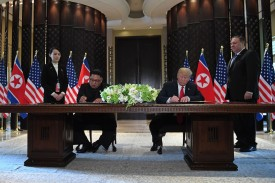 U.S. President Donald Trump and North Korean leader Kim Jong Un sign documents as U.S. Secretary of State Mike Pompeo and the North Korean leader's sister, Kim Yo Jong, look on in Singapore on June 12, 2018.