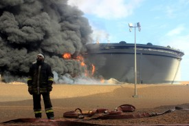A Libyan fireman stands in front of smoke and flames rising from a storage tank at an oil facility in northern Libya's Ras Lanuf region on January 23, 2016, after it was set ablaze earlier in the week following attacks launched by Islamic State jihadists to seize key port terminals.