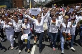 Venezuelan opposition leader Maria Corina Machado (C) takes part in a women's march in Caracas on May 6, 2017.