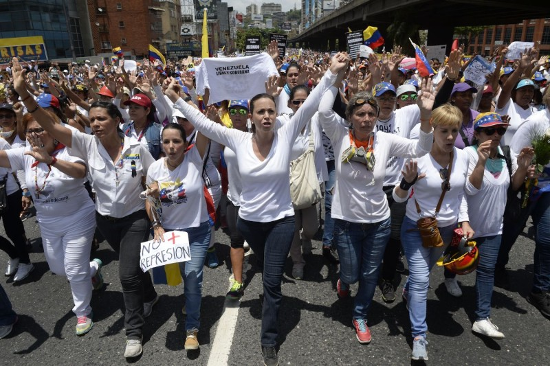 Venezuelan opposition leader Maria Corina Machado (C) takes part in a women's march in Caracas on May 6, 2017.