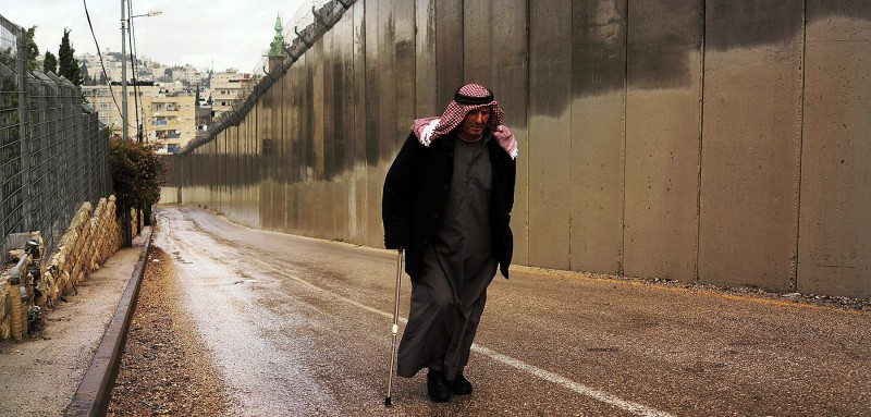 "A Muslim man walks by the ""separation barrier"" or ""security fence"" in East Jerusalem on November 27, 2014 in Jerusalem, Israel."