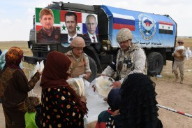 Members of the Russian military police hand out food aid to Syrians arriving in a convoy carrying displaced people in Idlib province, on June 1, 2018, with a banner on a Russian military vehicle seen in the background showing the portraits of Chechen leader Ramzan Kadyrov, Syrian President Bashar al-Assad , and Russian President Vladimir Putin.