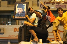 Iraqis celebrate with a picture of the Shiite cleric, Muqtada al-Sadr, after the general election in Baghdad on May 14, 2018.