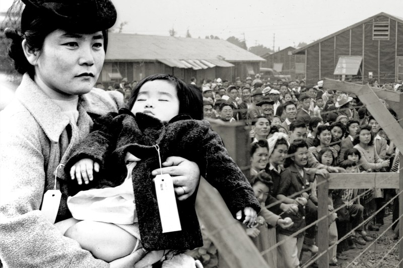 Left: A Japanese-American woman holds her sleeping daughter as they prepare to leave their home for an internment camp in 1942.  Right: Japanese-Americans interned at the Santa Anita Assembly Center at the Santa Anita racetrack near Los Angeles in 1942. (Library of Congress/Corbis/VCG via Getty Images/Foreign Policy illustration)