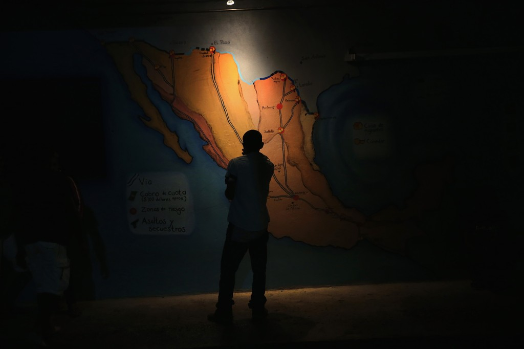 A Honduran immigrant inspects map of Mexico showing train routes leading north at a shelter for undocumented immigrants on September 14, 2014, in Tenosique, Mexico. (John Moore/Getty Images)