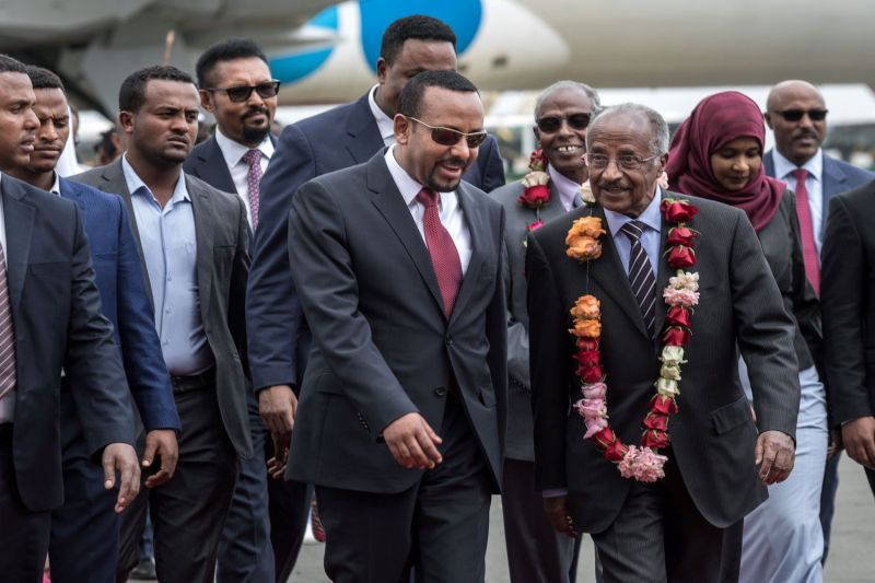 Eritrean Foreign Minister Osman Saleh Mohammed (R) walks with Ethiopian Prime Minister Abiy Ahmed (C) as an Eritrean delegation arrives for peace talks with Ethiopia at the international airport in Addis Ababa on June 26, 2018.