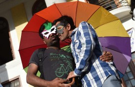 Indian gay rights activists belonging to the Karnataka Sexual Minorities Forum (KSMF) pose affectionately during a protest to demand the repeal of colonial-era laws on gay sex in Bangalore on July 2, 2014. (Manjunath Kiran/AFP/Getty Images)