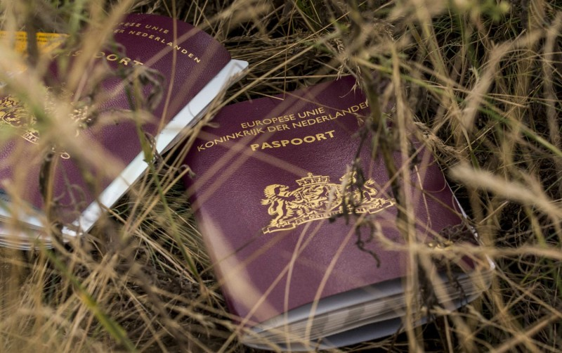 Two Dutch passports lie in a field among luggage, personal belongings and wreckage from Malaysia Airlines flight MH17 on Jul. 22, 2014, in Grabovo, Ukraine. (Photo by Rob Stothard/Getty Images.)