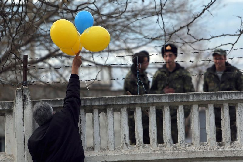 A pro-Ukrainian protester places balloons in the colors of the flag over the fencing where members of the Ukrainian military have been locked into their base by the Russians on Mar. 14, 2014 in Bakhchysarai, Ukraine. (Spencer Platt/Getty Images)