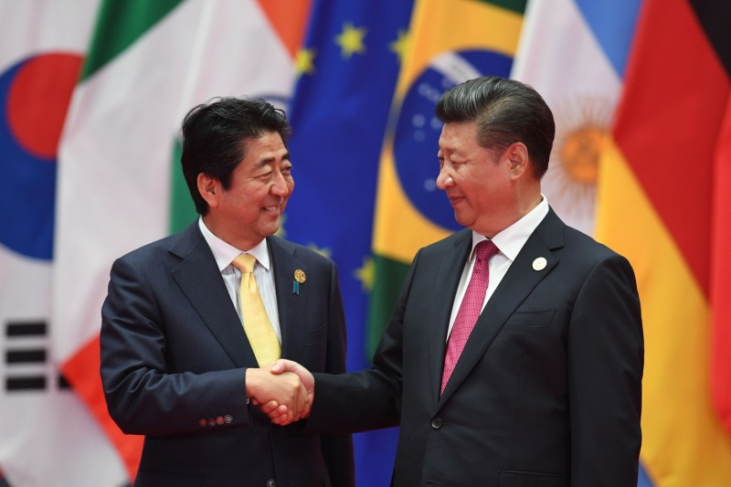 Japan's Prime Minister Shinzo Abe (L) shakes hands with China's President Xi Jinping (R) before the G20 leaders' family photo in Hangzhou on September 4, 2016. (GREG BAKER/AFP/Getty Images)