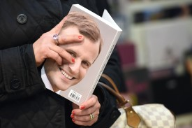 "A woman holds the book of Emmanuel Macron, head of ""En Marche"" political movement and presidential candidate, during a book signing session in a library in Bordeaux, on December 13, 2016. (NICOLAS TUCAT/AFP/Getty Images)"