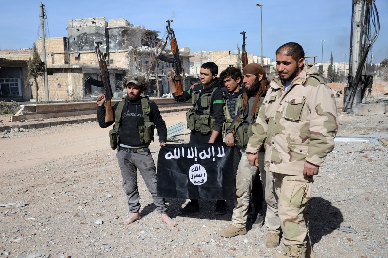 Rebel fighters pose with an Islamic State group flag as they advance on February 20, 2017, towards the city of Al-Bab, some 30 kilometres from the Syrian city of Aleppo.         (NAZEER AL-KHATIB/AFP/Getty Images)