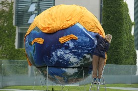 An activist prepares a balloon painted to look like planet Earth and decorated with orange hair and eyebrows in the likeness of U.S. President Donald Trump during a climate protest prior to a meeting of European Union leaders at the Chancellery on June 29, 2017 in Berlin, Germany. (Sean Gallup/Getty Images)
