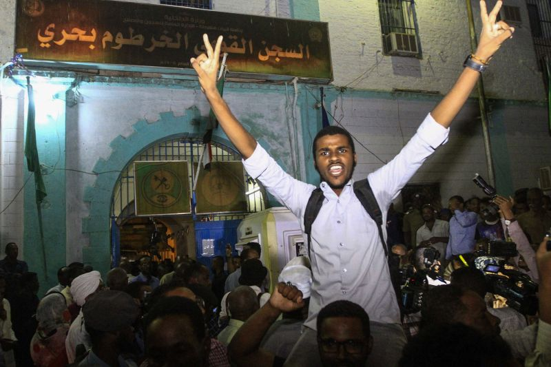 Family members shout slogans as they wait outside the Kobar prison in north Khartoum to welcome their loved ones after Sudan released dozens of opposition activists Feb. 18 who were arrested in January when authorities cracked down on protests against rising food prices. (Ebrahim Hamid/AFP/Getty Images)