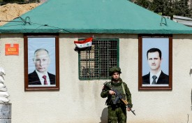 A picture taken on March 1, 2018 shows a member of the Russian military police standing guard between the portraits of Syrian President Bashar al-Assad (R) and Russian President Vladimir Putin (L) hanging outside a guard-post at the Wafideen checkpoint on the outskirts of Damascus neighbouring the rebel-held Eastern Ghouta region. (LOUAI BESHARA/AFP/Getty Images)