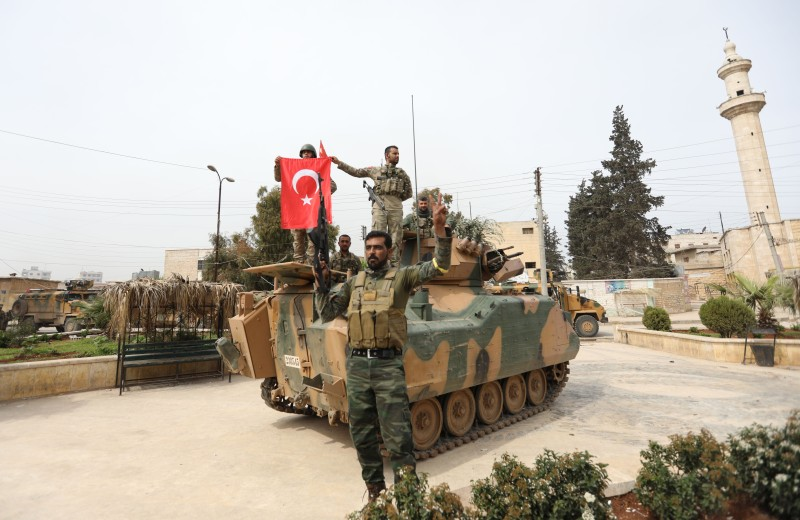 Turkish soldiers and Ankara-backed Syrian Arab fighters pose for a group photo in the Kurdish-majority city of Afrin in northwestern Syria after seizing control of it on March 18, 2018.(Omar Haj Kadour/AFP/Getty Images)