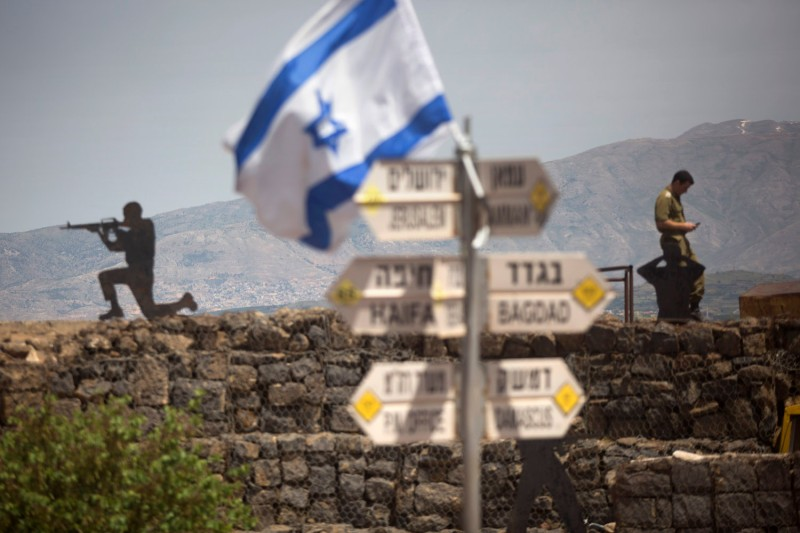 An Israeli soldier stands next to a sign on Mount Bental, near the the Syrian border of the Israeli-annexed Golan Heights, on May 10. (Photo by Lior Mizrahi/Getty Images)