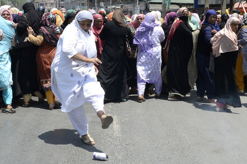 A Kashmiri 'Anganwadi', a government sponsored child and mother care worker, kicks away a chili grenade thrown by Indian police during an anti-government protest in Srinagar on May 30, 2018.  (TAUSEEF MUSTAFA/AFP/Getty Images)