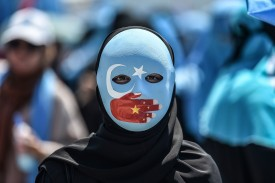 A demonstrator wearing a mask painted with the colors of the flag of East Turkestan and a hand bearing the colors of the Chinese flag attends a protest  in front of the Chinese consulate in Istanbul, on July 5, 2018.(OZAN KOSE/AFP/Getty Images)