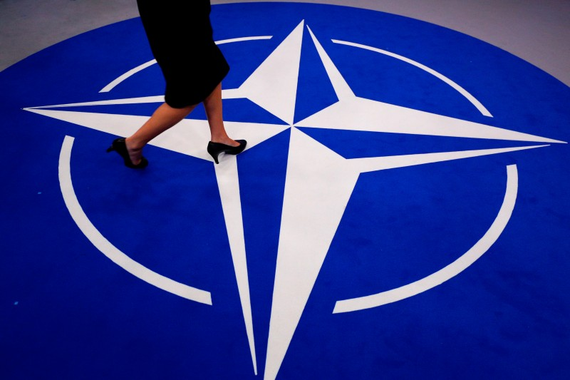 A woman walks across a carpet ahead of the NATO summit in Brussels, on July 11, 2018. (GEOFFROY VAN DER HASSELT / AFP)