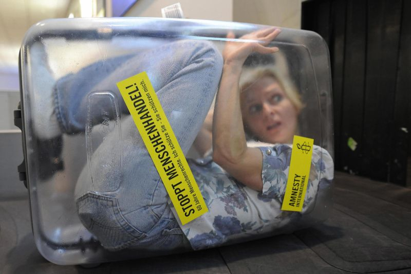 "A woman is locked up in a transparent suitcase reading ""Stop Human Trafficking! 60 Years of Human Rights"" on a luggage belt at the airport in Munich, Germany, on December 11, 2008. The Human Rights organization Amnesty International staged the action to commemorate the 60th anniversary of the Universal Declaration of Human Rights."