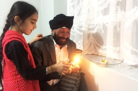 Sikh community leader Rawail Singh lights the Diwali lamps with his daughter Komal on Oct. 18, 2017, in Kabul. (Ruchi Kumar for Foreign Policy)