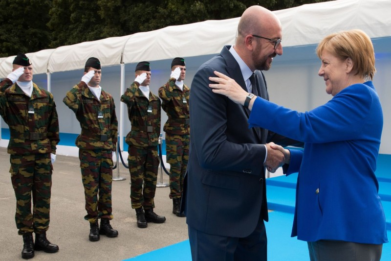 Belgian Prime Minister Charles Michel greets German Chancellor Angela Merkel for a working dinner in Brussels on July 11, 2018, during the NATO summit.