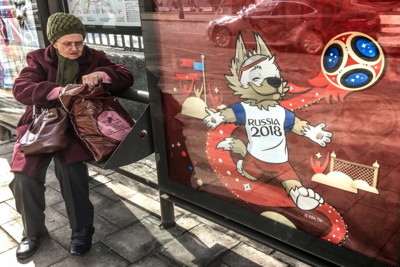 An older woman sits at a bus stop next to a poster featuring Zabivaka, the official mascot of the 2018 World Cup, in downtown Moscow on April 4. (Mladen Antonov/AFP/Getty Images)