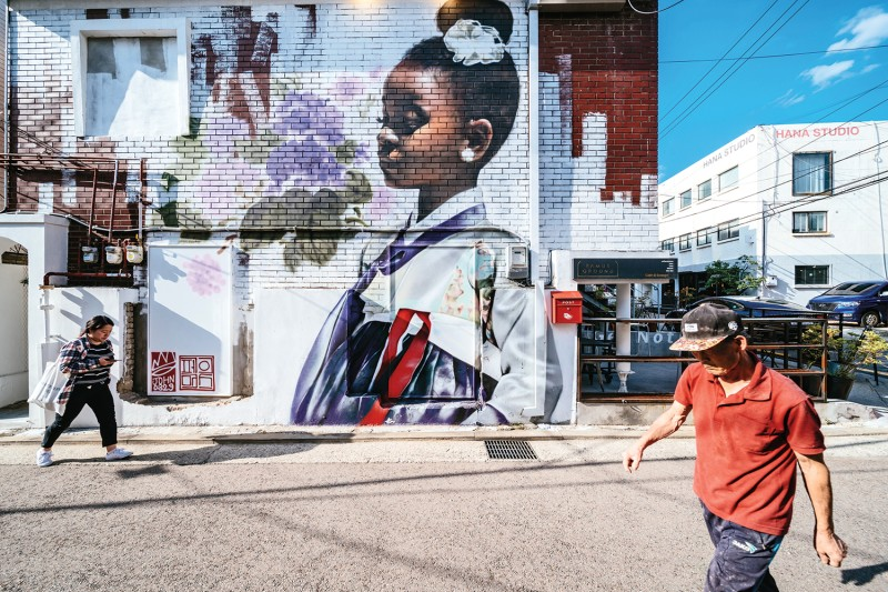 The graffiti artist Chris Shim, aka Royyal Dog, makes multiculturalism the focus of a series of murals in his home city of Seoul, including this one in an alley, and around the world. (Jun Michael Park for Foreign Policy)