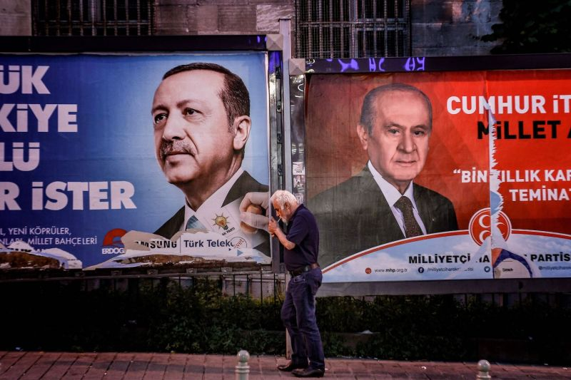 A pedestrian lights a cigarette as he walks past banners with portraits of Turrkish President Recep Tayyip Erdogan (L) and the leader of Nationalist Movement Party (MHP) Devlet Bahceli in Istanbul on June 19.
