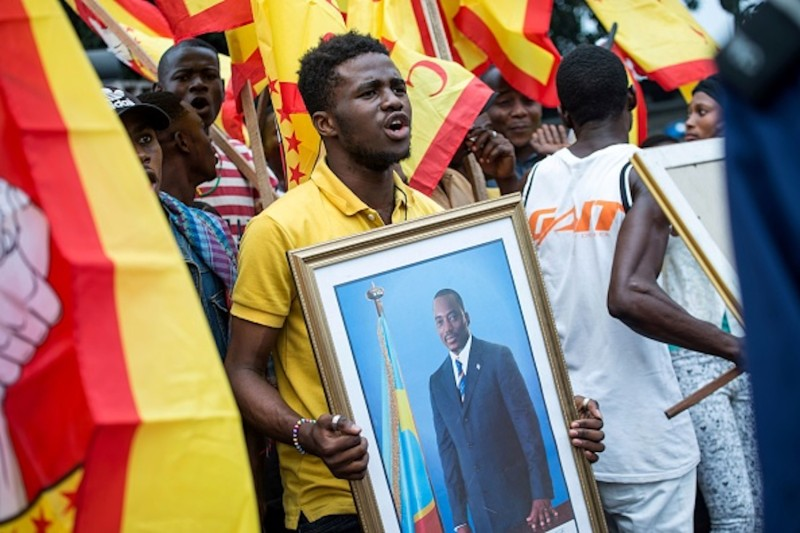 A supporter of Congolese leader Joseph Kabila holds a picture of the president outside Parliament in Kinshasa on July 19.