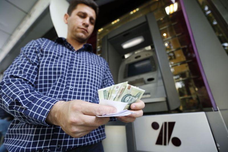 A man withdraws Iranian rials from an ATM in Tehran on July 31. (Atta Kenare/AFP/Getty Images)