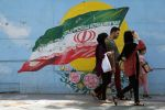 Iranians walk past a mural in Tehran on Aug. 8. (Fatemeh Bahrami/Anadolu Agency/Getty Images)