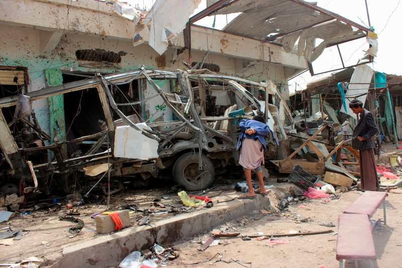 Yemenis gather next to the destroyed bus at the site of a Saudi-led coalition air strike, that targeted the Dahyan market the previous day in the Huthi rebels' stronghold province of Saada on August 10, 2018. (STRINGER/AFP/Getty Images)
