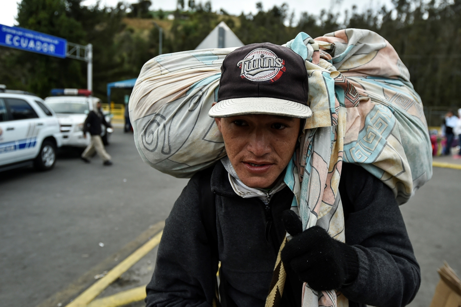 A Venezuelan migrant outside the Ecuadorean migration office at the Rumichaca International Bridge between Tulcan, Ecuador, and Ipiales, Colombia, on Aug. 20. Colombia's government expressed concern last week that tightened Ecuadorian entry requirements for Venezuelans would leave thousands stranded in Colombia. LUIS ROBAYO/AFP/Getty Images