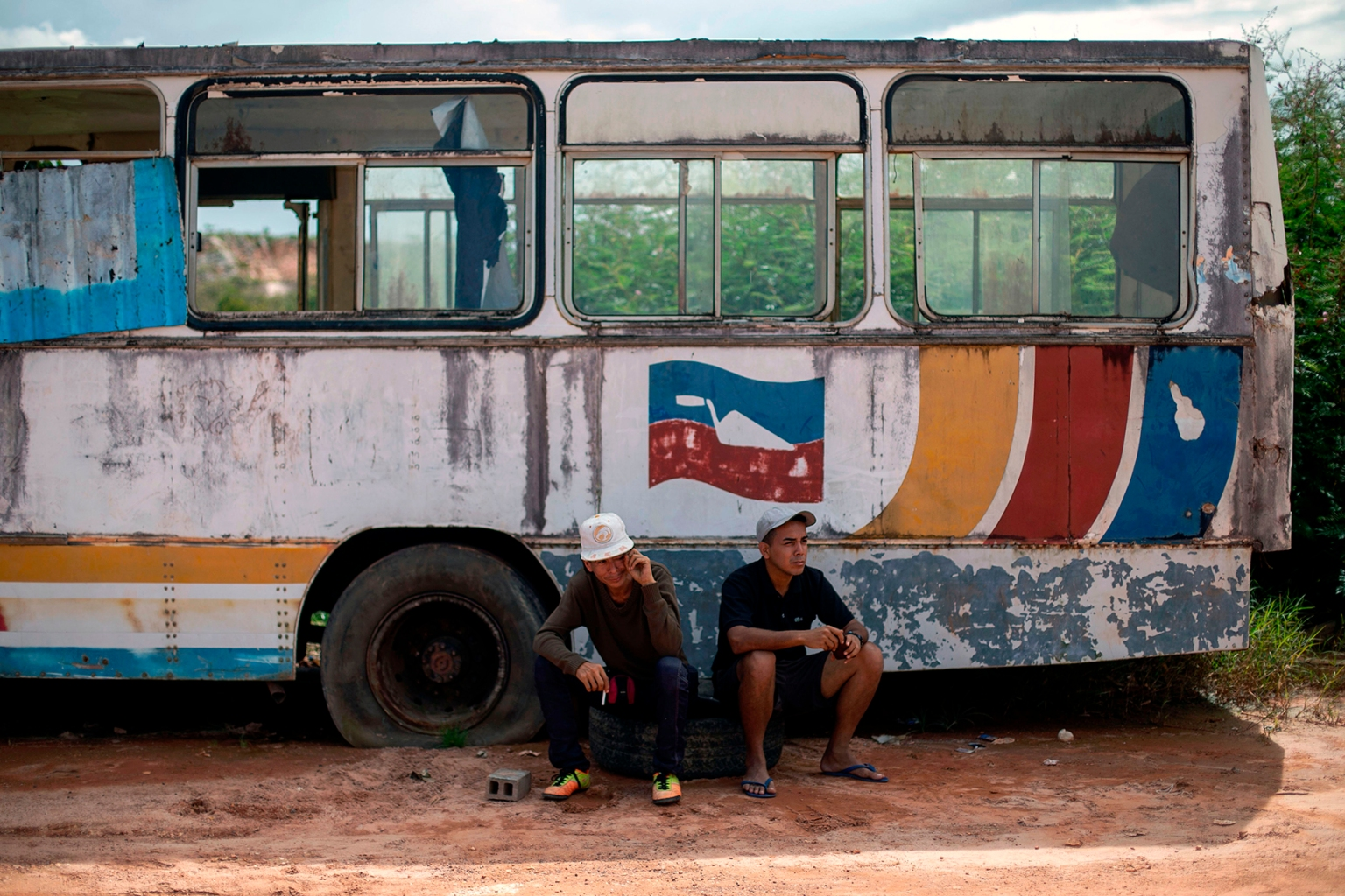 Venezuelans rest on the side of the road near Pacaraima, Brazil, on Aug. 20. Pacaraima residents recently drove Venezuelan migrants out of improvised camps amid growing tensions in the border town. MAURO PIMENTEL/AFP/Getty Images
