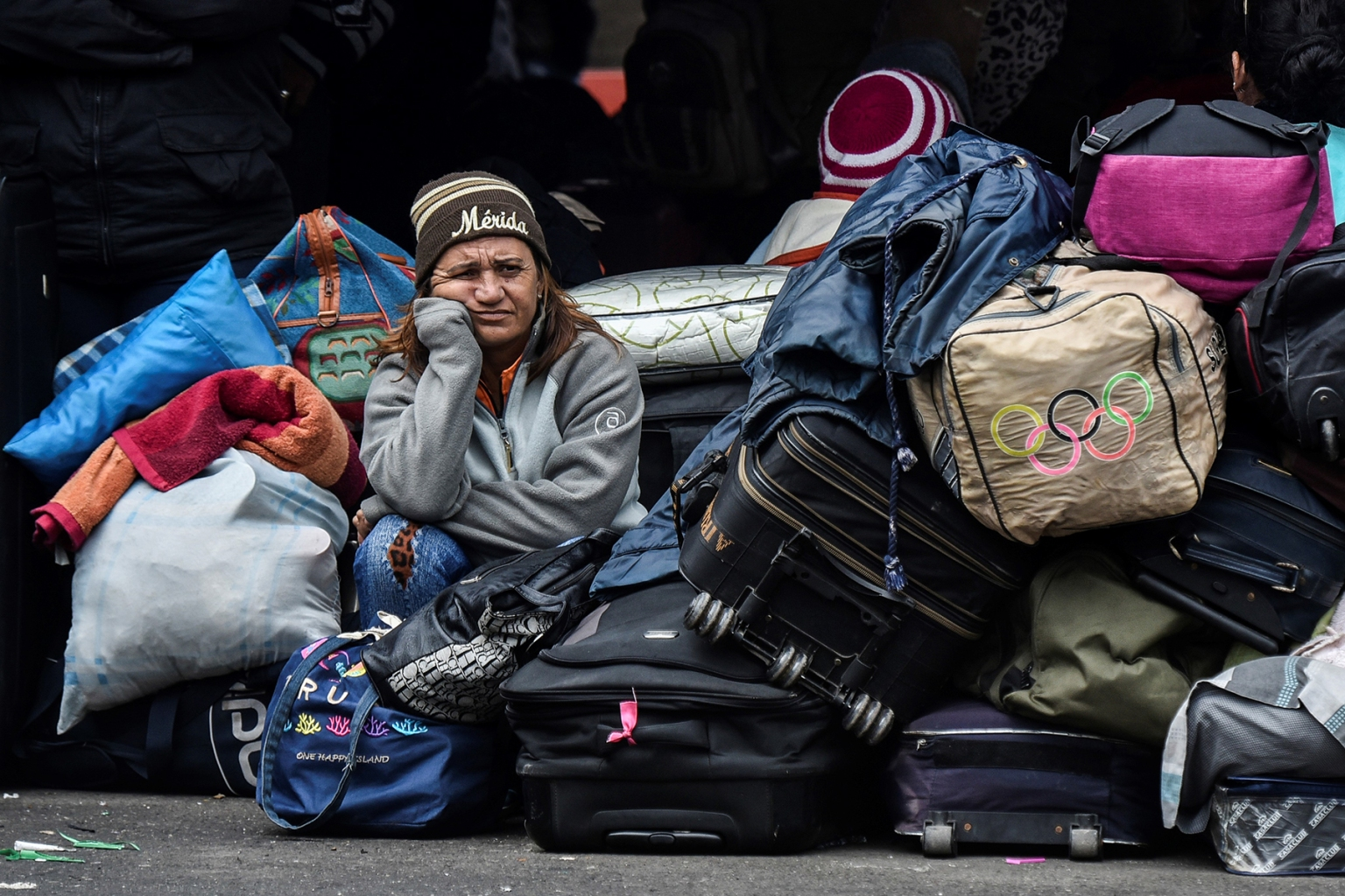 A Venezuelan woman waits outside the Colombian migration office along the Rumichaca International Bridge before crossing from Ipiales in Colombia to Tulcan in Ecuador on Aug. 20. LUIS ROBAYO/AFP/Getty Images