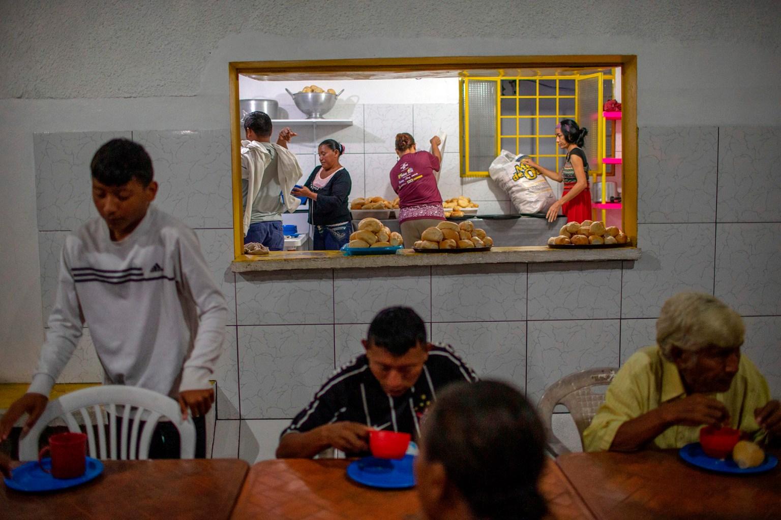 Venezuelans eat breakfast at Spanish priest Jose Lopez Fernandez de Bobadilla's parish in Pacaraima, Brazil, on Aug. 21. Venezuelans continue to cross the border despite the violent anti-migrant riot that took place last week in Pacaraima. (MAURO PIMENTEL/AFP/Getty Images)
