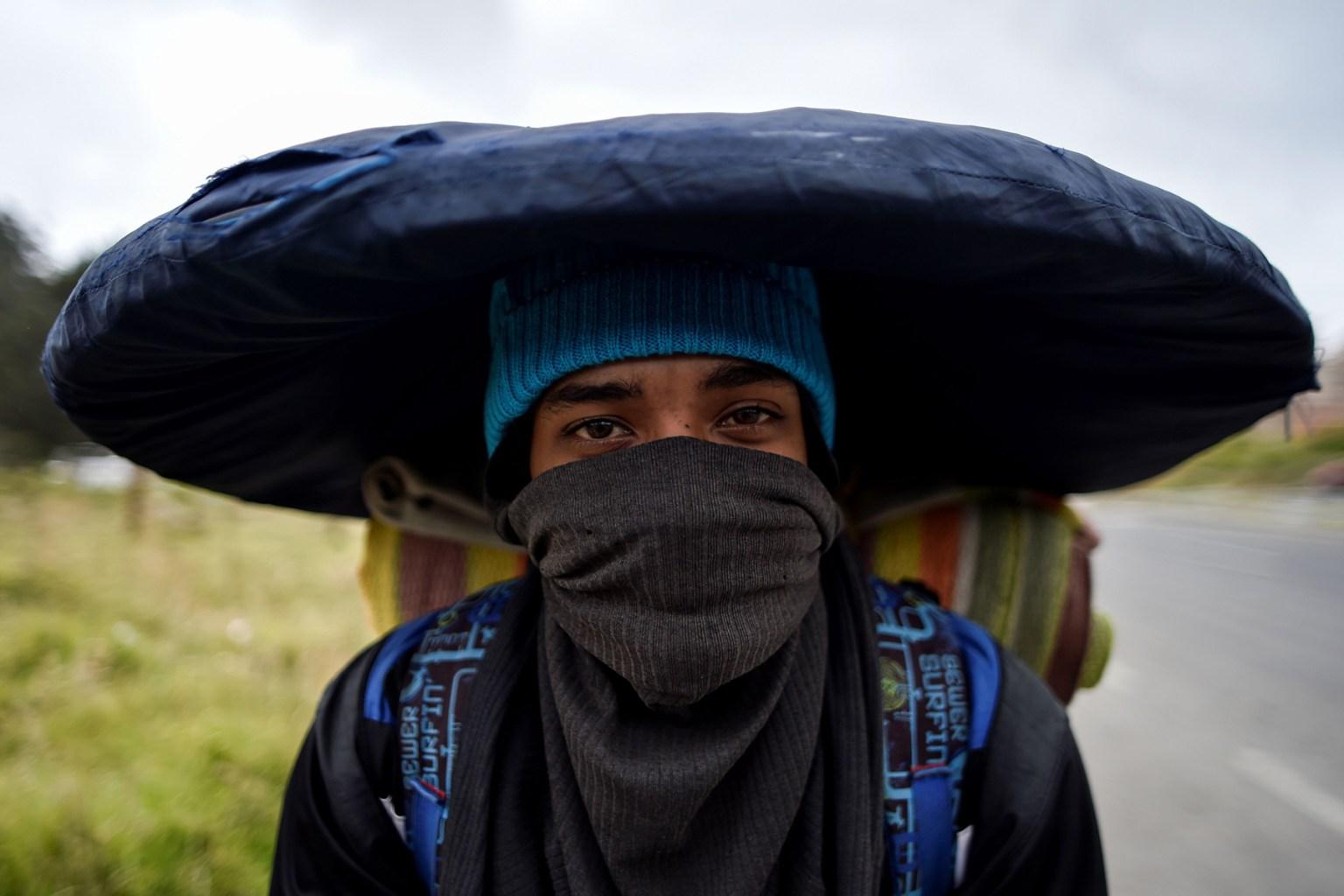 A Venezuelan migrant carries his belongings along the Pan-American Highway in Tulcan, Ecuador, on Aug. 21, 2018. LUIS ROBAYO/AFP/Getty Images