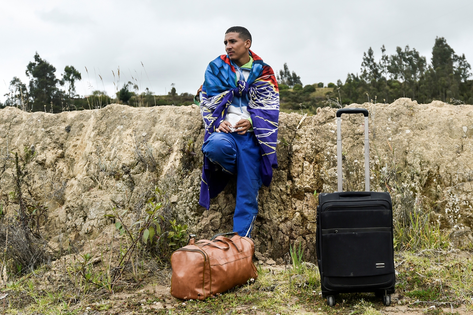 A Venezuelan migrant rests on the Pan-American Highway in Tulcan, Ecuador, on Aug. 21. He was on his way to Peru after crossing from Colombia. LUIS ROBAYO/AFP/Getty Images