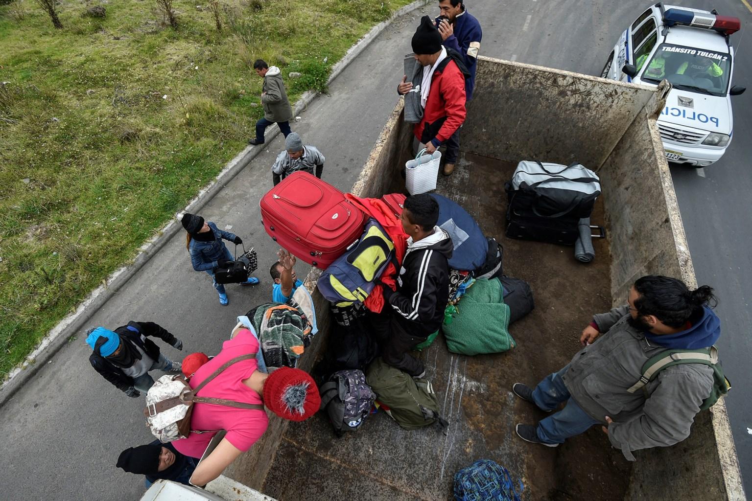 Venezuelan migrants board a truck on their way to Peru in Tulcan, Ecuador, on Aug. 21. LUIS ROBAYO/AFP/Getty Images