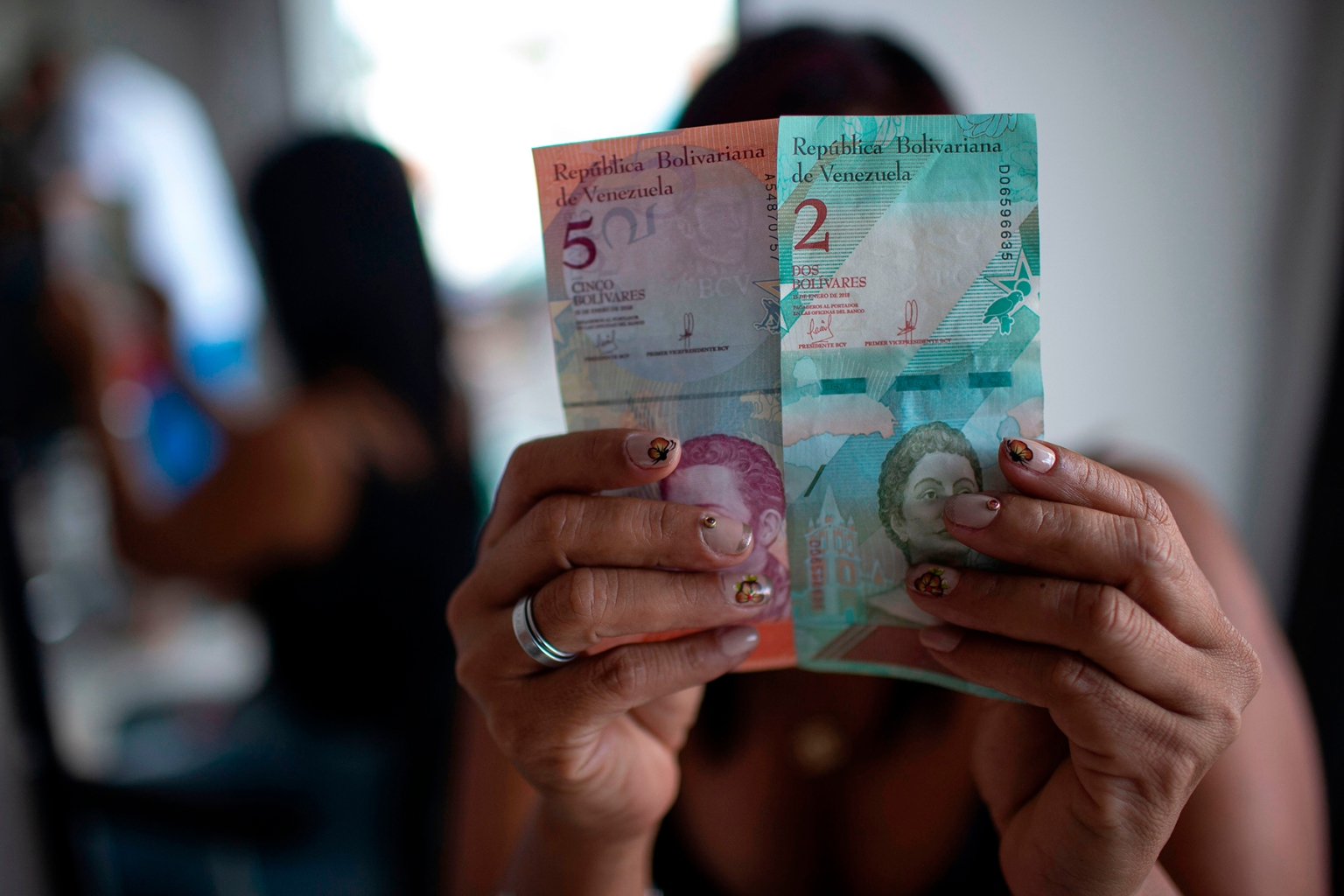 A woman shows bills of the new Venezuelan currency—the Bolivar Soberano worth 100,000 old Bolivars—at a barbershop in Pacaraima, Brazil, on Aug. 21. Venezuela's ruling Socialists United party issued new currency on Aug. 20 in an attempt to stem hyperinflation, which critics expect to make the country's dire economic situation worse. MAURO PIMENTEL/AFP/Getty Images