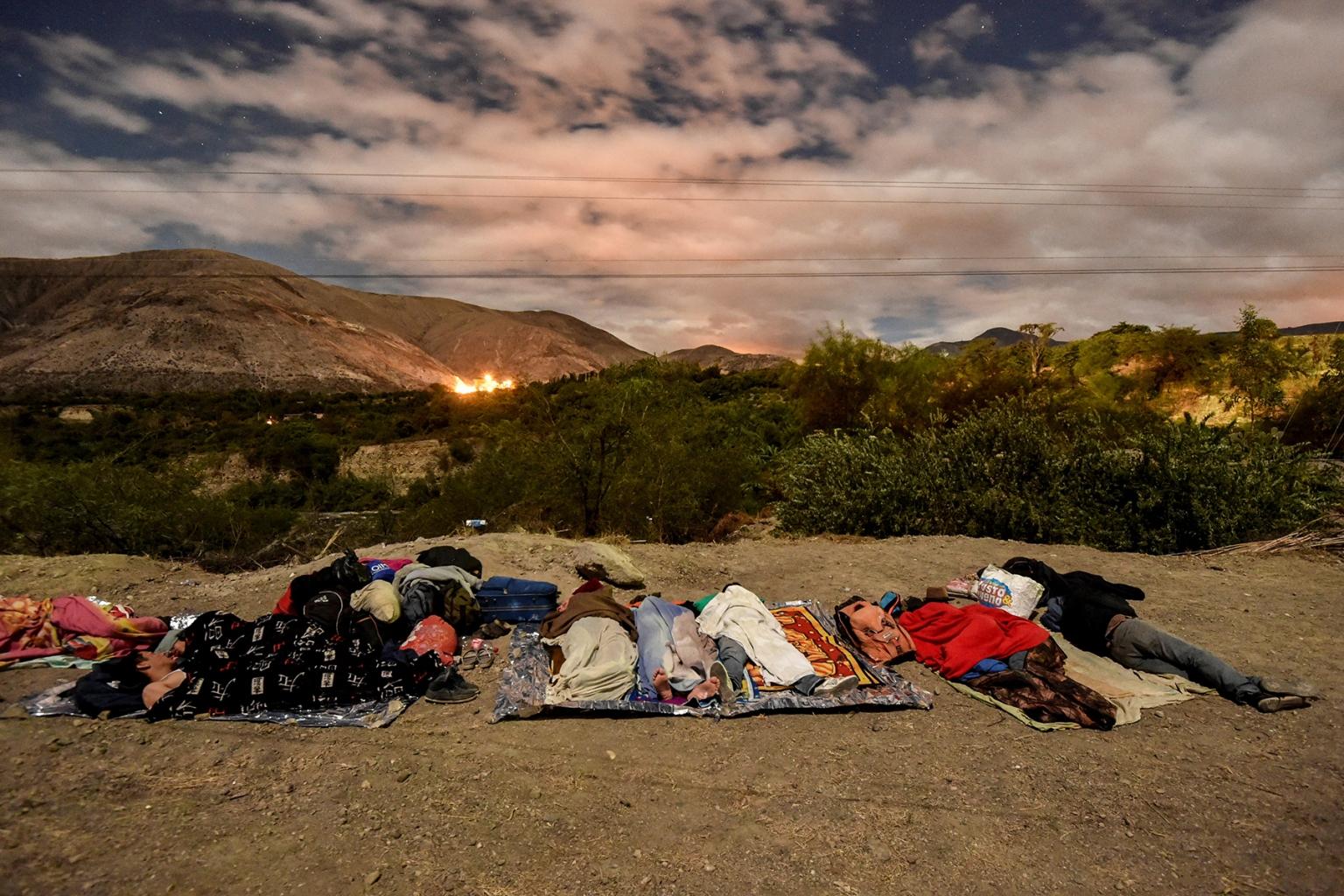 Venezuelan migrants on their way to Peru sleep along the Pan-American Highway between Tulcan and Ibarra in Ecuador on Aug. 22. LUIS ROBAYO/AFP/Getty Images
