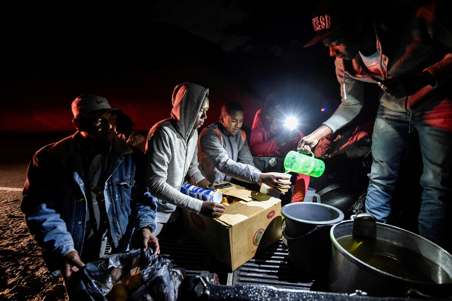 Venezuelan migrants en route to Peru receive food as they rest along the Pan-American Highway between Tulcan and Ibarra in Ecuador after entering the country from Colombia on Aug. 21. LUIS ROBAYO/AFP/Getty Images