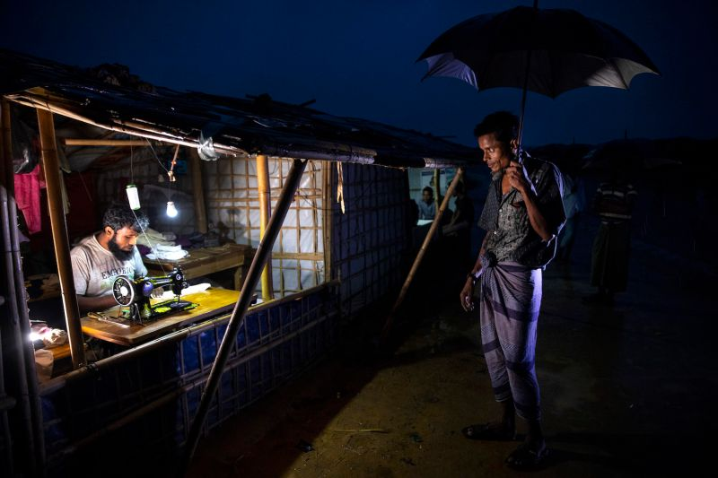 A man stands under an umbrella as monsoon rains arrive in Balukhali refugee camp in Cox's Bazar, Bangladesh, on Aug. 28. More than 700,000 Rohingya refugees have fled to Bangladesh. (Paula Bronstein/Getty Images)