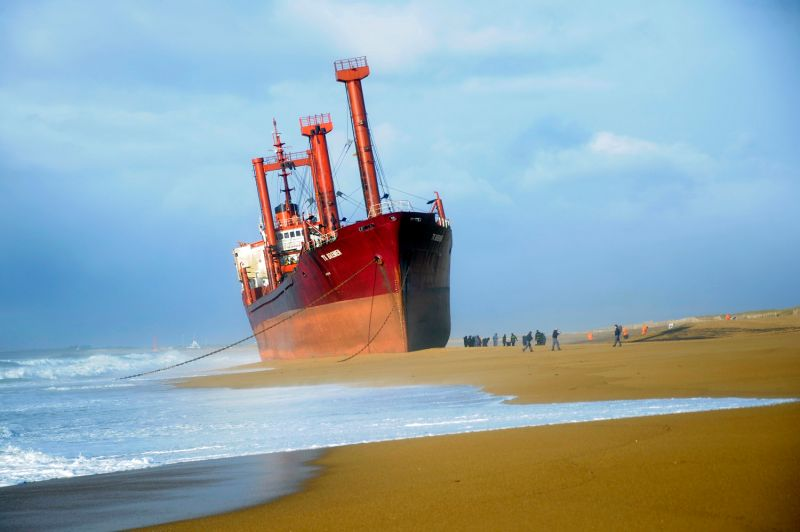 Rescue workers stand next to the TK Bremen, a cargo ship stranded on Kerminihy beach in Erdeven, France, on Dec. 16, 2011. (Damien Meyer/AFP/Getty Images)