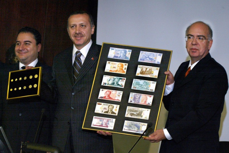 Recep Tayyip Erdogan holds with the president of Turkey's Central Bank, Sureyya Serdengecti, a board featuring the new Turkish lira samples 25 October 2004 while Economy Minister Ali Babacan shows new coins during their presentation at central bank headquarters in the capital Ankara. (TARIK TINAZAY/AFP/Getty Images)