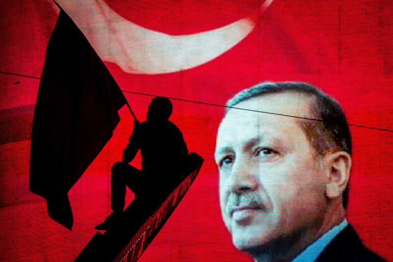 A supporter of Turkish President Recep Tayyip Erdogan waves a flag against an electronic billboard during a rally in Ankara on July 18, 2016.(Chris McGrath/Getty Images)